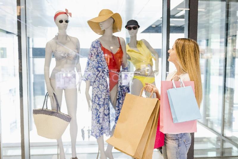 Mulher carregando várias sacolas no shopping para e olha a vitrine. Não vai resistir às armadilhas da mente.