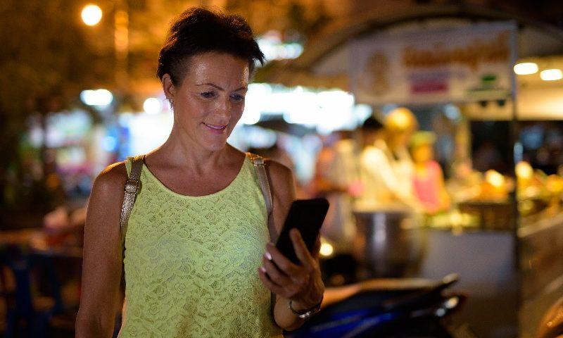 Jovem senhora está numa feira noturna e consulta o celular.