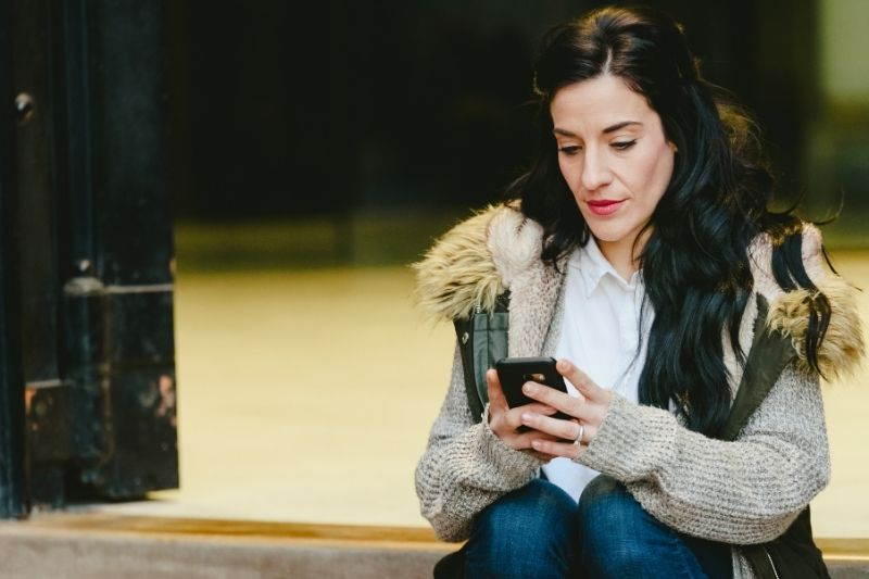 Mulher consulta o aplicativo do beOne para ver a sua situação financeira.